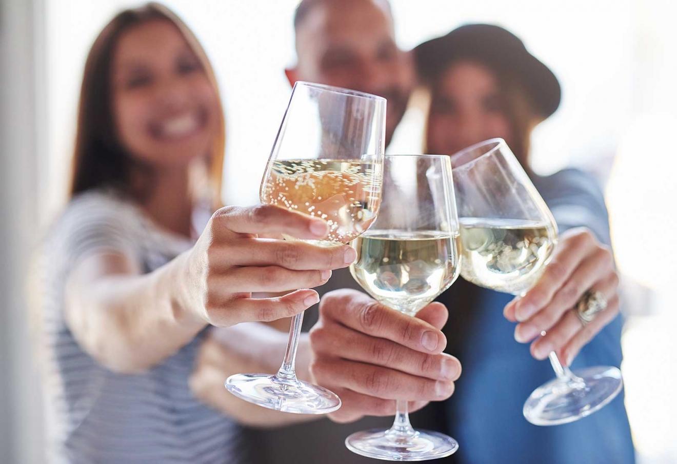 toasting-wine-glasses-with-people-behind-them-8GPRKXK